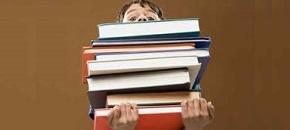 Scolaro che trasporta una pesante quantità di libri