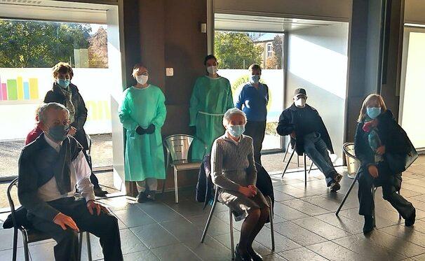 Persone in attesa di ricevere il vaccino antinfluenzale all'interno della Biblioteca di Castellanza